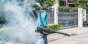 Worker spraying insecticide on a residential street