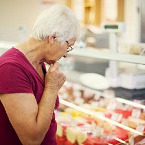 Woman examining cheeses at market.