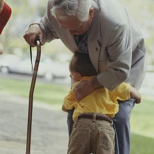 Grandfather with cane hugged by child